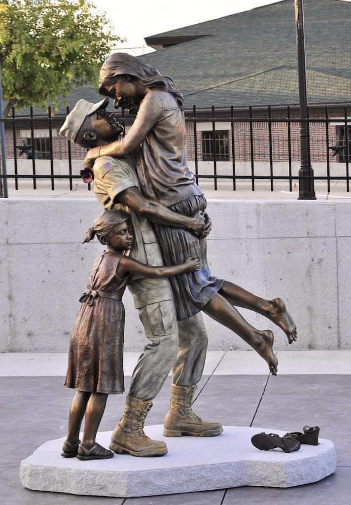 Sutton Betti, military deployment homecoming, reuniting after military deployment, returning home, bronze military sculpture, US Coast Guard sculpture, military family sculpture, after the war statue, bronze sculptor Sutton Betti, life size bronze sculpture, multi color patina, American Veterans Park statue, West Point, Nebraska, Coast Guard Family